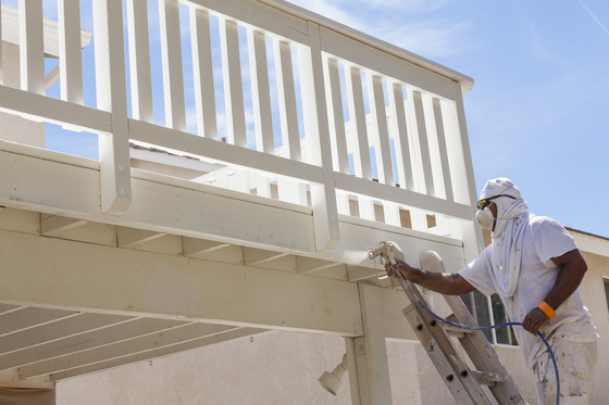 Picture of our employee with respirator on while painting a deck on the back of a house white in Philadelphia, PA